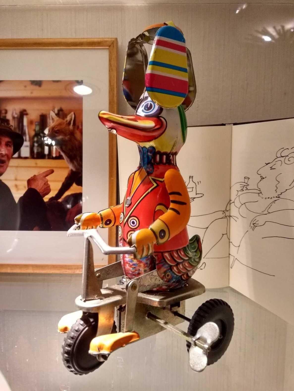 Blick in eine Glasvitrine mit Spielzeug von Tomi Ungerer und der Künstler, der dem Fuchs predigt